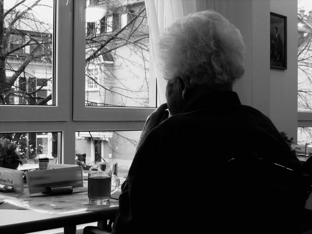 persona anciana viendo por la ventana